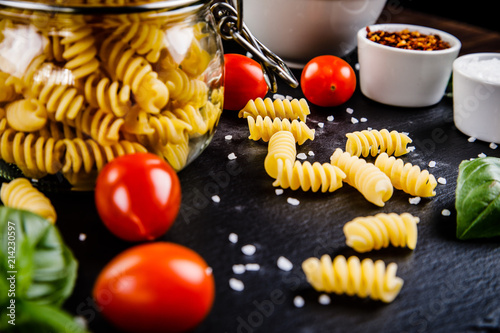 Valokuvatapetti Raw pasta with spices on black stone on wooden background
