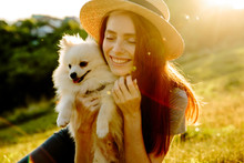 The Cute Red-haired Woman In A Hat With A Spitz-dog Sitting In The Park. Beautiful Sunset Light. Background Toning For Instagram Filter.