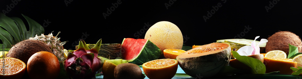 Fototapeta Assortment of tropical fruits with leaves of palm trees and exotic plants