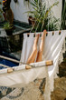 Close-up of a legs of beautiful sporty young woman rest and swinging in white hammock near blue pool. Tropical private house. Cheerful lady enjoy her vacation after hard office day to day work.