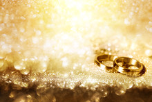 Wedding Rings On Festive Golde...