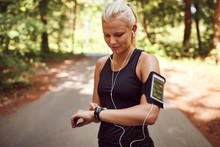 Fit Woman Setting Her Sports Watch Before A Forest Run