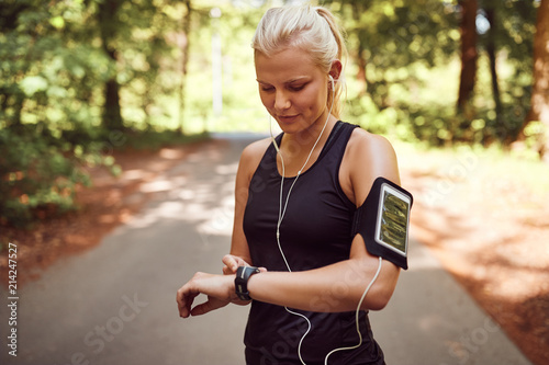 Valokuva  Fit woman setting her sports watch before a forest run