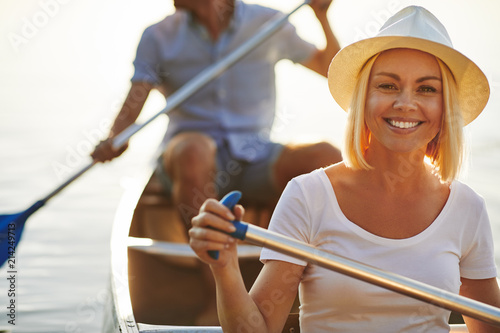 Fotografia Smiling young woman canoeing with her boyfriend on a lake