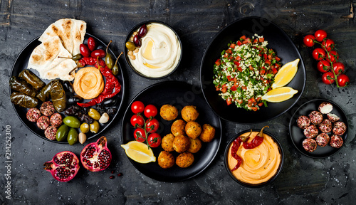 Arabic traditional cuisine. Middle Eastern meze platter with pita, olives, hummus, stuffed dolma, labneh cheese balls in spices. Mediterranean appetizer party idea