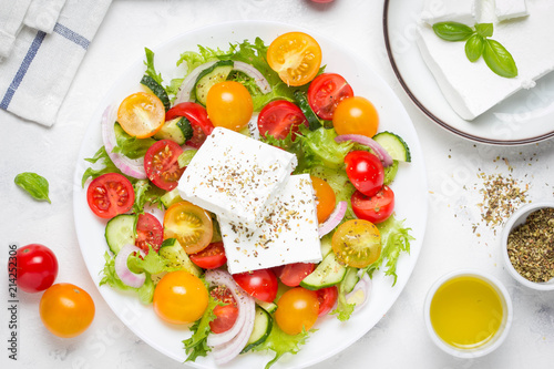 Fototapety, obrazy: Greek salad with colorful cherry tomatoes red and yellow, cucumber, onion, lettuce and large piece of feta cheese with herbs. In white plate on light background