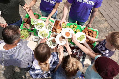 Photo Volunteers serving food for poor people outdoors, above view