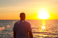 A Man Stands With His Back Looking At The Sea And The Sunset
