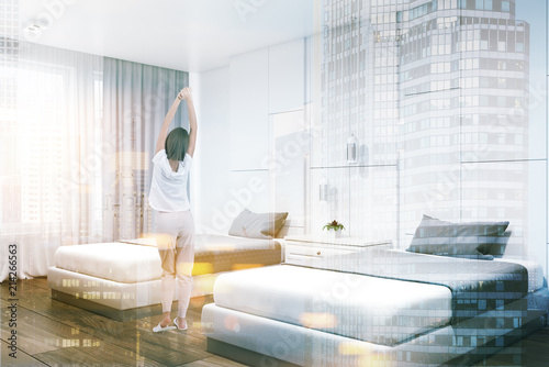 Photo  White hotel suite corner, two beds, woman
