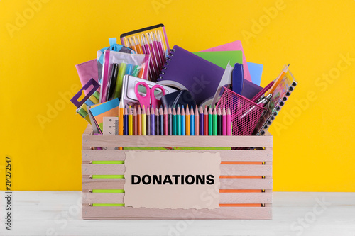 Fotomural  Box with various school and office supplies with a sign on a bright yellow background