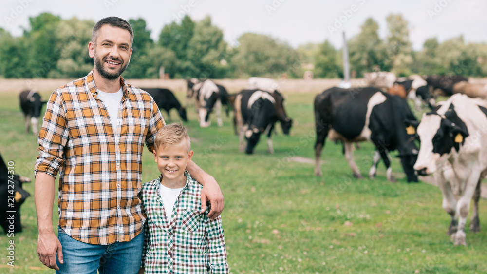 Fototapety, obrazy: happy father and son smiling at camera while standing near grazing cattle at farm