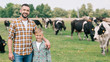 canvas print picture - happy father and son smiling at camera while standing near grazing cattle at farm