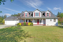 Cute Home Exterior With Red Shutters On A Summer Day.