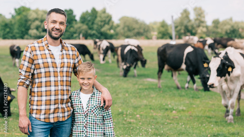 Foto  happy father and son smiling at camera while standing near grazing cattle at far
