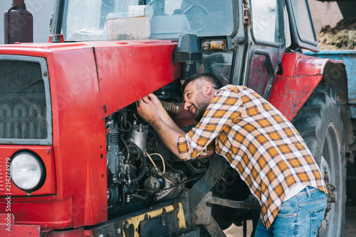 Photo handsome middle aged farmer in checkered shirt repairing tractor