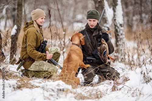 two hunters with rifles in a snowy winter forest.