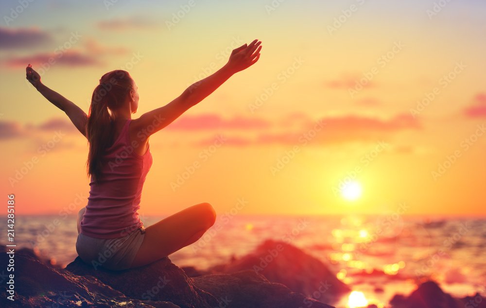 Fototapeta Relaxation And Yoga At Sunset - Girl With Open Arms Looking Ocean