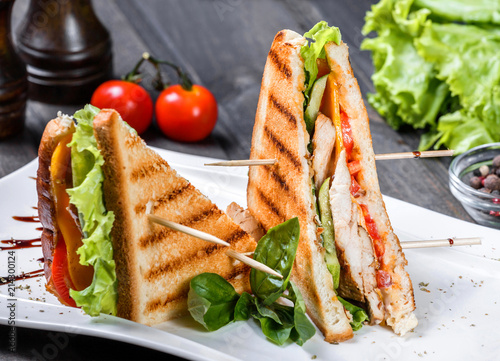 Club sandwich with cheese, cucumber, tomato, chicken meat and lettuce on dark wooden table. Delicious snacks, sandwiches