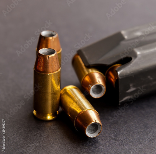 Photo Three hollow point bullets next to a loaded pistol magazine on a black backgroun