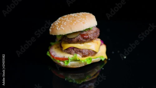 The sesame bun is falling on the top of burger. Slow motion. Black mirror surface