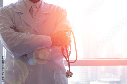 Fotografiet  Professional medical physician doctor in white uniform gown coat hand holding stethoscope in clinic hospital