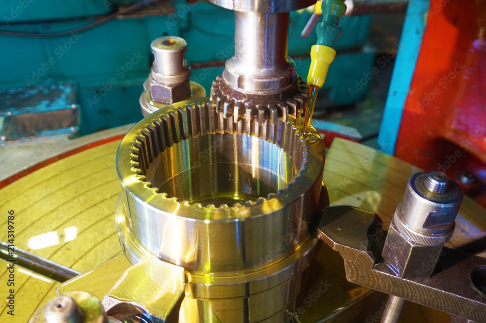 Fototapety, obrazy: Gear cutter. Cutting the tooth on the tooth with a slotting machine with oil cooling. Metal-working industry.