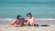 Father and son laying down on seashore, play with snorkeling equipment