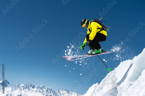 Fotomural  A skier in full sports equipment jumps into the precipice from the top of the glacier against the background of the blue sky and the Caucasian snow-capped mountains