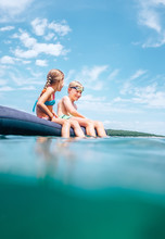 Two Childs Have A Fun When Swim On Inflatable Mattress In The Sea Lagoon
