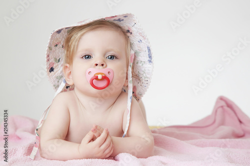 Studio portrait of adorable baby girl with pacifier wearing a hat Wallpaper Mural