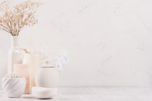 Organic Homemade White Cosmetics Products In Different Ceramics Bowls, Pink Salt And Small Dried Flowers  On White Wooden Background, Border.