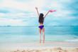 Beautiful bikini asian teenage jumping on the beach
