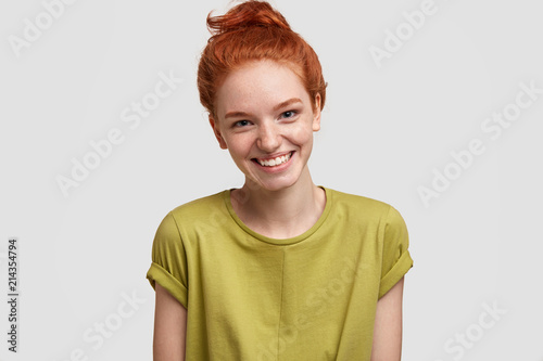 Fotografia  Positive ginger femae with freckled skin, broad smile, dressed in casual green t shirt, isolated over white background, expresses happiness as has date with boyfriend