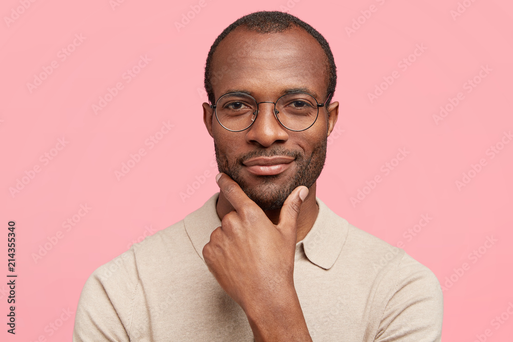 Fototapeta Headshot of serious dark skinned male boss holds chin, contemplates about succeessful agreement, looks mysteriously at camera, dressed in casual t shirt, stands indoor against pink background