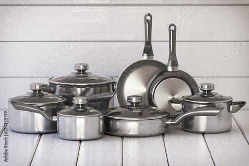 Obraz na plátně Set of stainless pots and pan with glass lids on the white wooden background