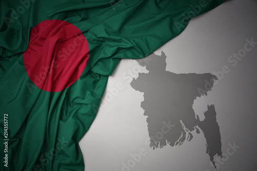 Photo waving colorful national flag and map of bangladesh.