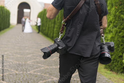 Obraz Professional wedding photographer takes pictures of the bride and groom in garden, the photographer in action with two cameras on a shoulder straps. - fototapety do salonu