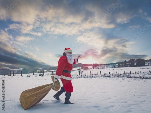 Papiers peints Arctique Santa Claus with a bag of gifts walking along a snow-covered field, on the horizon a winter forest and sunlight.