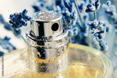 Photo Closeup metallic spray perfume bottle framed with blue lavender herb, yellow aroma extract