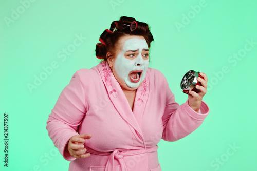 femme ronde et drôle avec bigoudis tenant un réveil