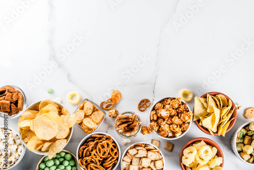 Variation different unhealthy snacks crackers, sweet salted popcorn, tortillas, Fototapet