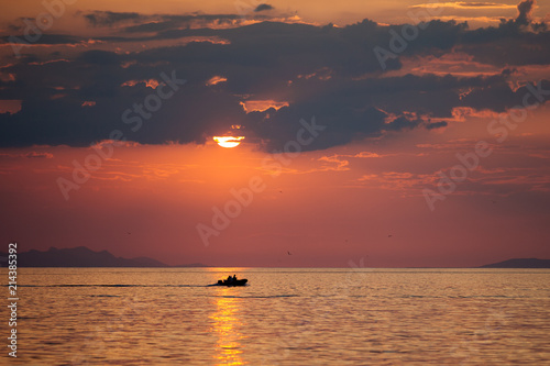 Papiers peints Corail Fishing boat passes the sun path reflection in the sea on sunrise