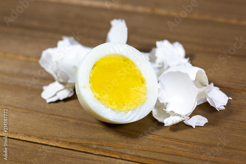 Fotografie, Obraz  Half a hardboiled egg with the shells laying on the kitchen table
