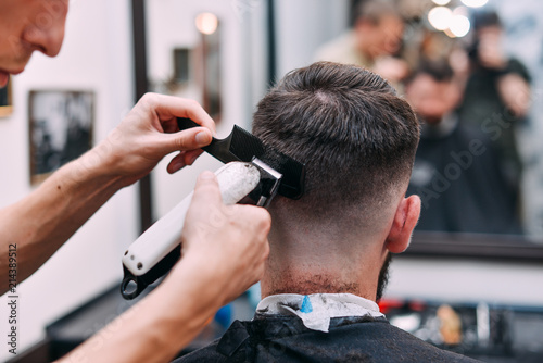 A man is hanging around in a beauty salon. Haircut and styling in barbershop. Men's care for beard and hair.
