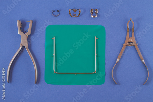 Tools for installing the cofferdam lying on a blue background. Wallpaper Mural