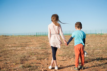 Small Brother And Sister Refugees Holding Hands Standing Among Desert On State Border