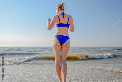 Fotobehang womenART Woman in a blue swimsuit by the sea. A palm print in the form of sand on the priest at the woman.