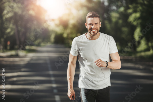 Fotografiet  Waist up portrait of happy young man jogging in park in morning