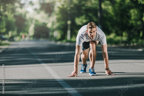 Full length of runner crouching at start line ready for competition Canvas Print