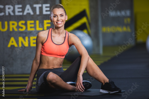 Cheerful fit lady is sitting on floor in sport studio and grinning. She is enjoying spending time actively and training indoors. Happy woman is resting after work out